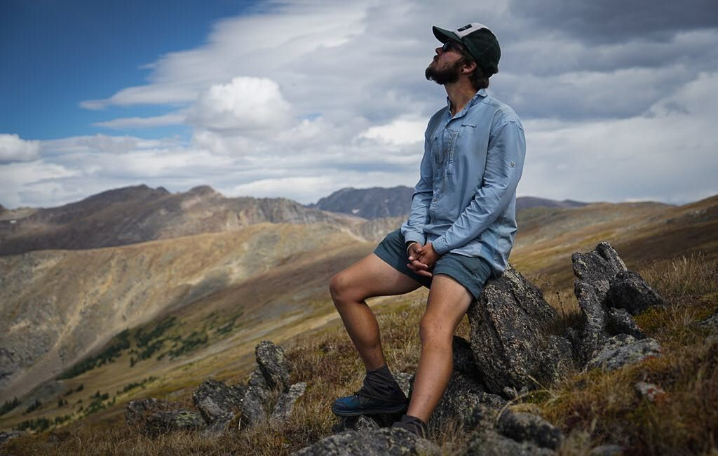 male hiker resting on a rock wearing a long-sleeve polyester button hiking shirt