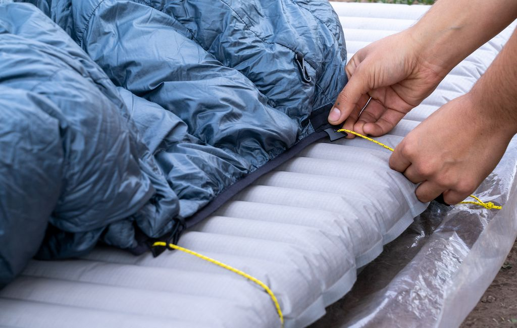Showing how to attach a quilt to a sleeping pad