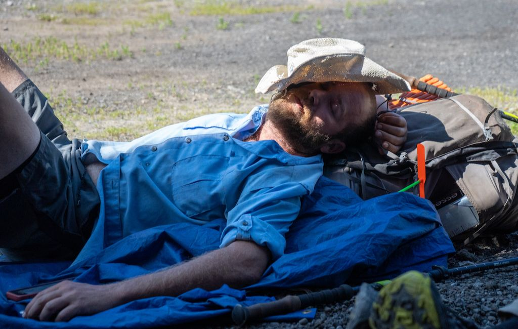 hiker laying in the sun underneath straw hat