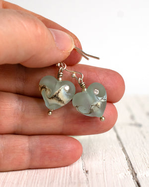 small aqua blue art glass bead heart earrings with cubic zirconia in hand for size