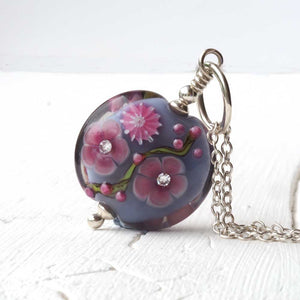 Grey floral lampwork art glass bead with cubic zirconia close up