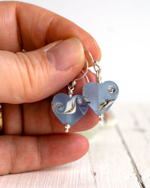 Small sapphire blue lampwork glass heart earrings by Judith Johnston in hand for size