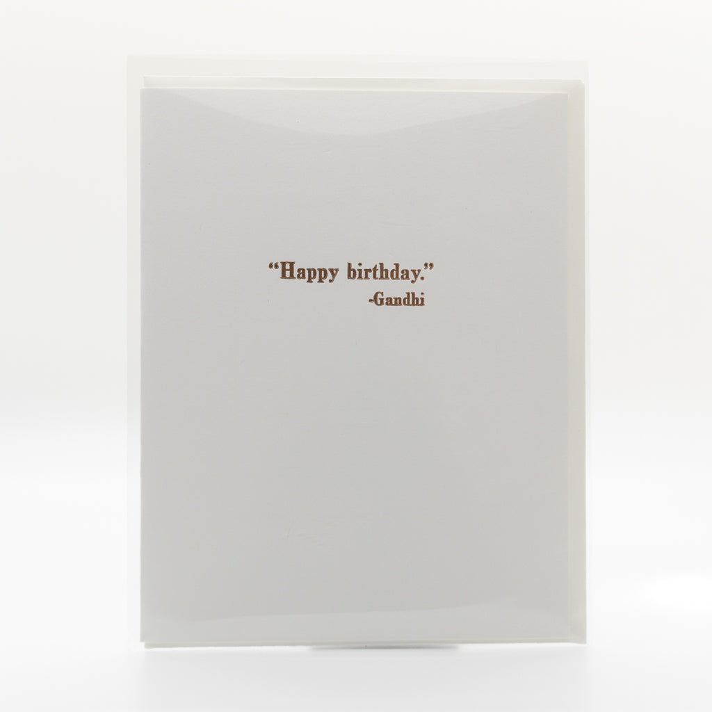 "Simple white card with brown text saying ""Happy birthday."" -Gandi and a white envelope"