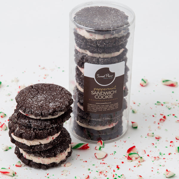 3 Peppermint sandwhich holiday cookiesstacked vertically beside a container of 6 Peppermint sandwhich holiday cookies