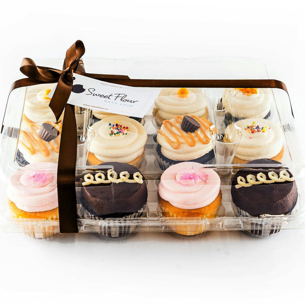 one dozen assorted cupcakes in clamshell with brown ribbon
