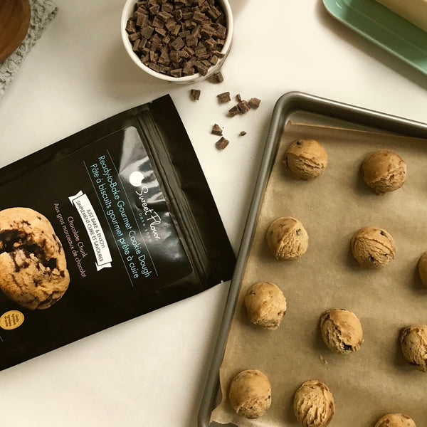 holiday cookie dough balls on a baking tray beside an empty bag of cookie dough mix
