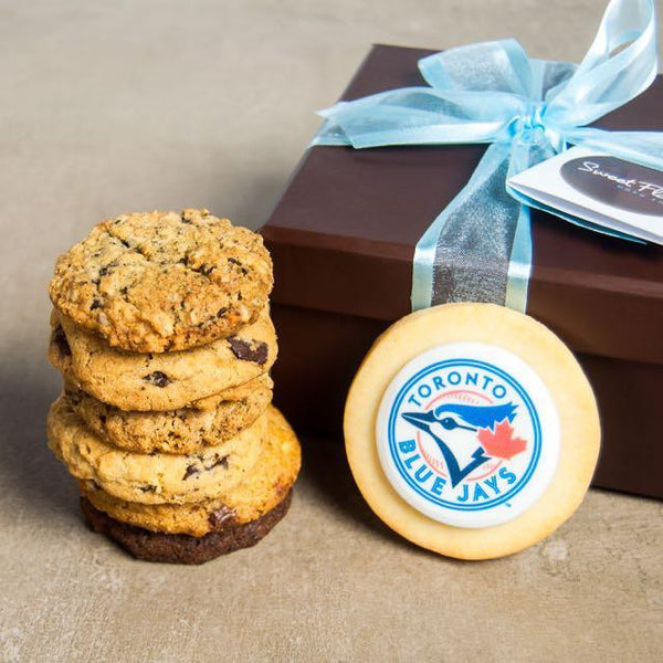 6 cookies stacked in front of Toronto Blue Jays logo cookie and brown Sweet Flour gift box with blue ribbon