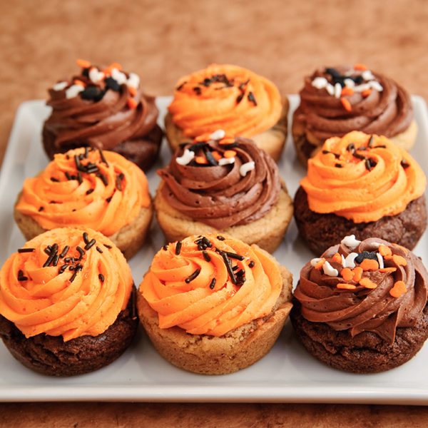 Halloween cookie cupcakes with chocolate chunk and chocolate rainbows cookies with orange and brown icing