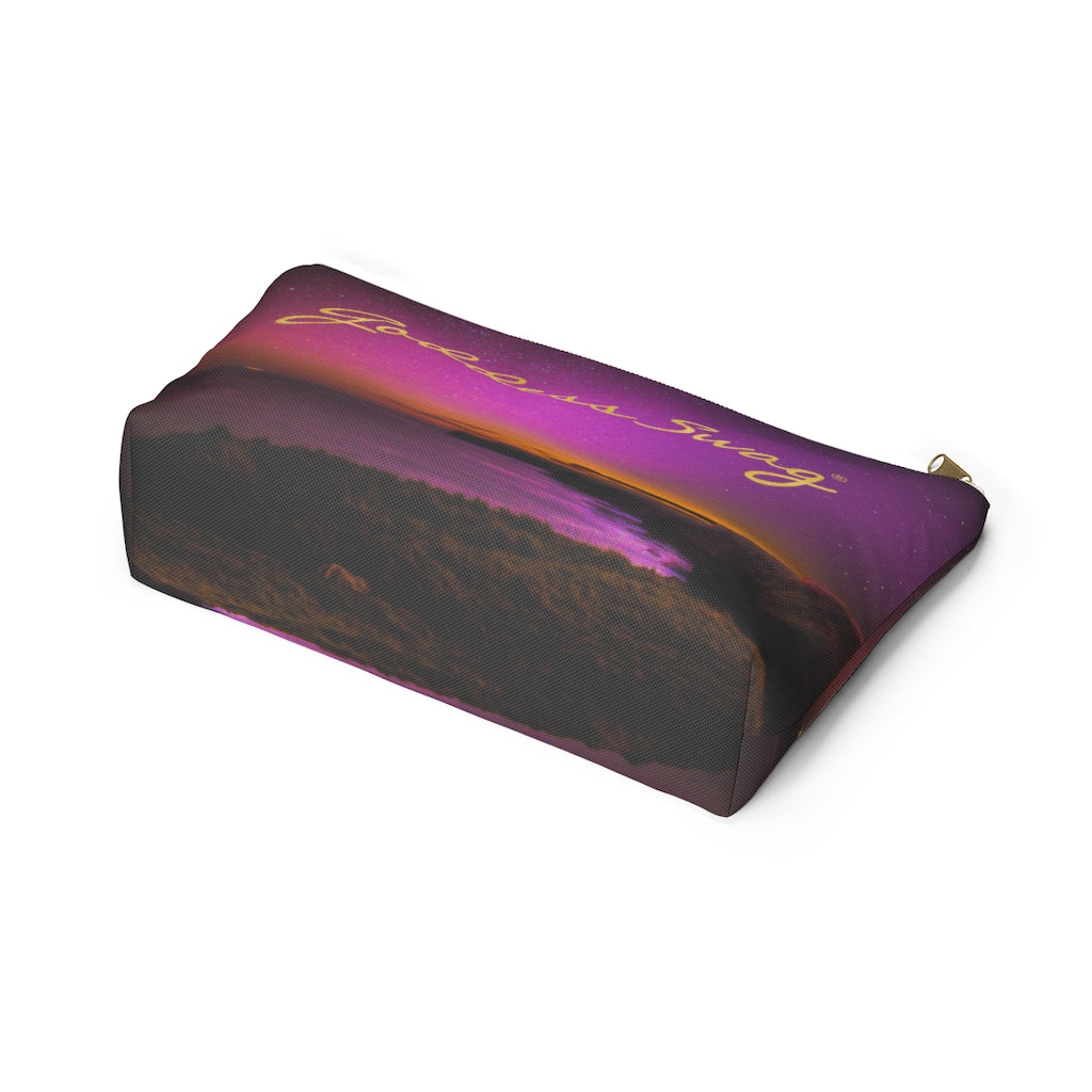 This is a picture of an accessory pouch or cosmetic bag with a background image of a purple gradient color sky with light spots that resemble stars.  Goddess Swag wording is in gold on one side of the bag only.  There is an option of a black or a white zipper, and a large or a small bag. Toward the bottom of the bag is some orange color representing a sun that just set.