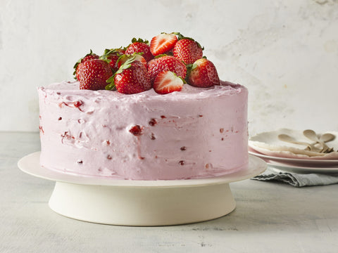 strawberry lemonade layer cake with pink frosting and strawberry jam filling