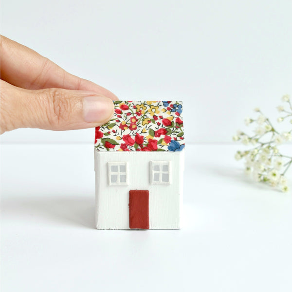 Handmade white small wooden cottage ornament decorated with Emma and Georgina Liberty of London cotton tana lawn red floral fabric.
