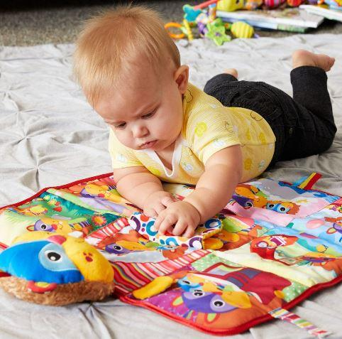 baby playing on colourful beaver-themed baby playmat
