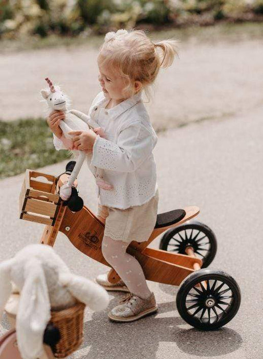 Little girl riding wooden tricycle made by Kinderfeet