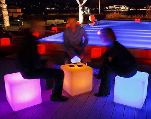Photograph showing people sitting on large LED cube seats at nighttime