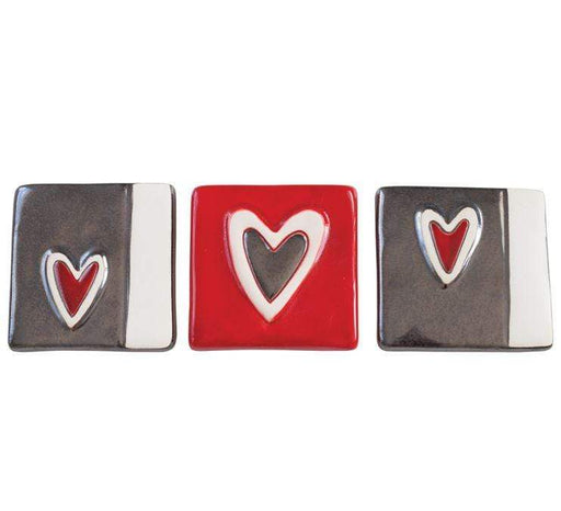 set of three small ceramic tiles, each with a stylized heart