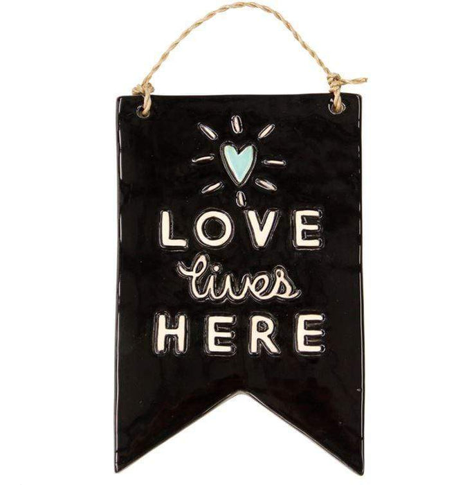 "Ceramic wall plaque with the words ""Love lives here"""