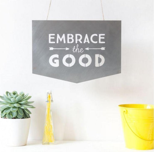 "Small steel sign with the words ""embrace the good""."