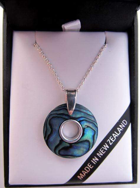 Round doughnut shaped paua pendant with silver inlay and chain shown in a gift box.