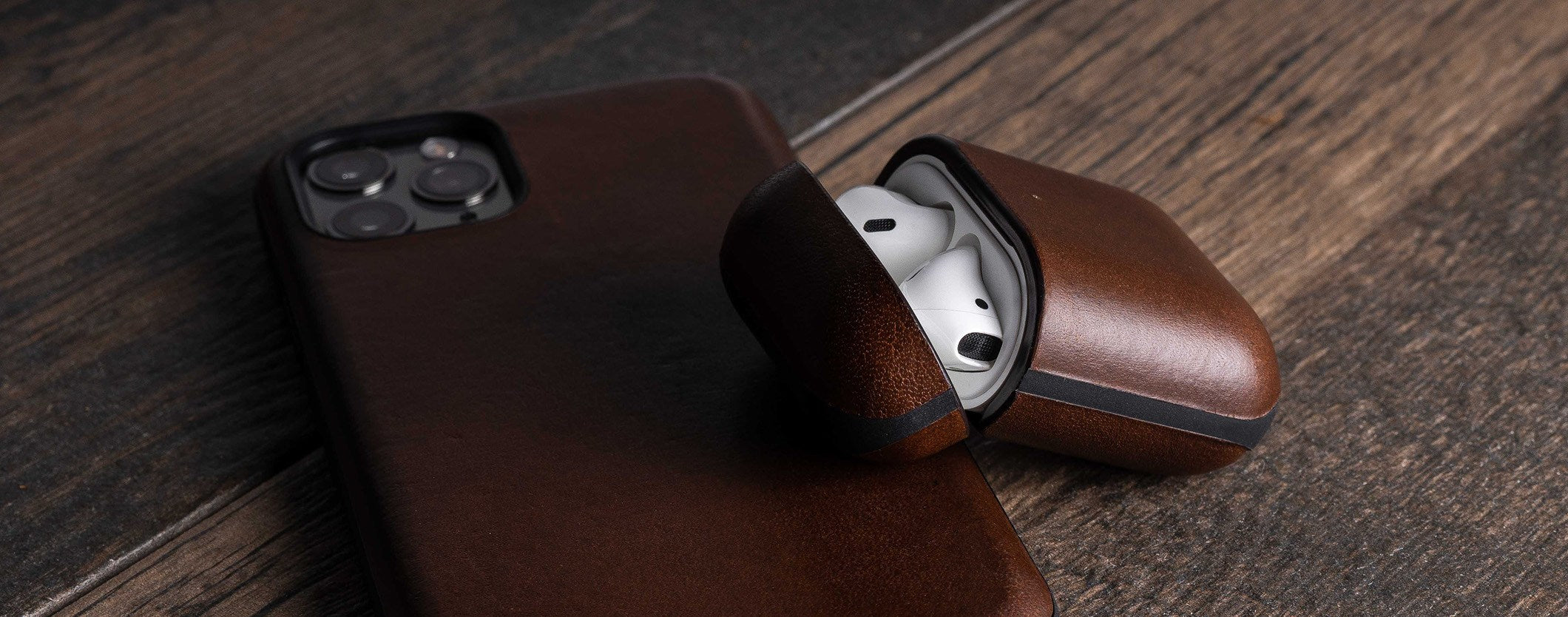 Open Rugged Case in Rustic Brown displaying Apple AirPods sitting on iPhone 11 Pro