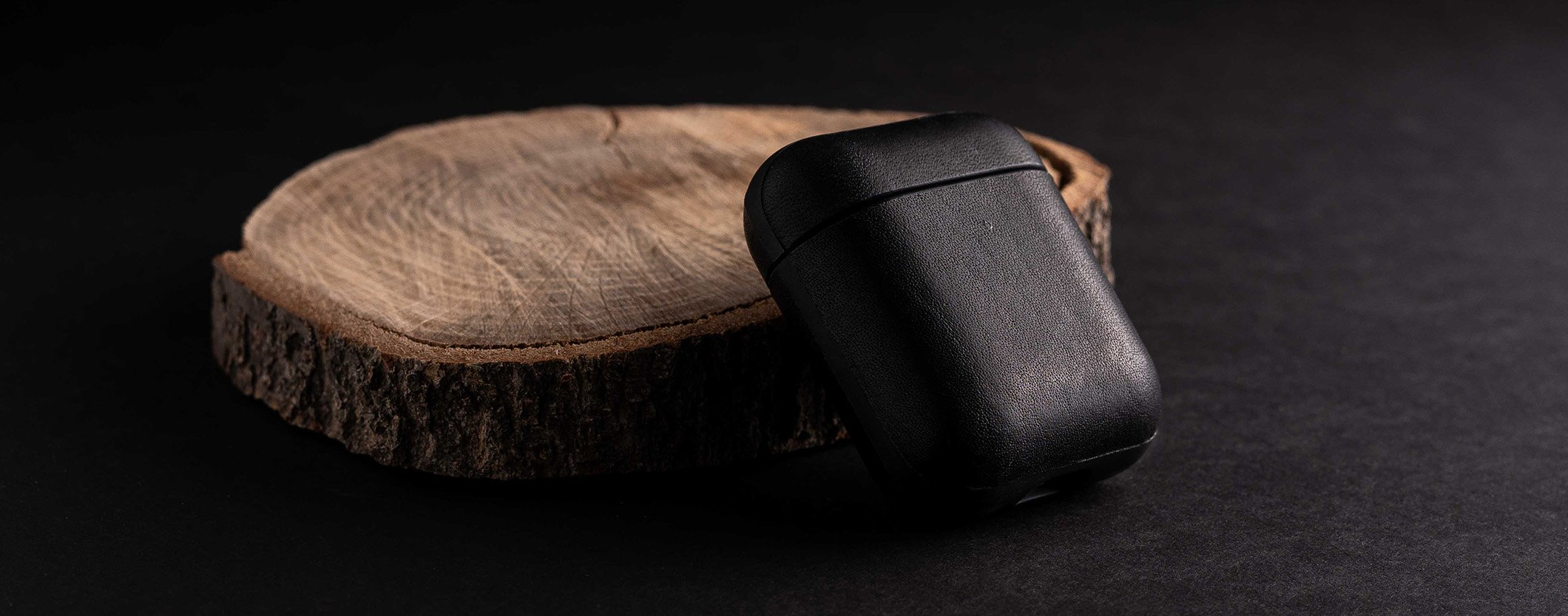 Close up of Rugged Case in Rustic Brown for Apple Airpods on a wooden table