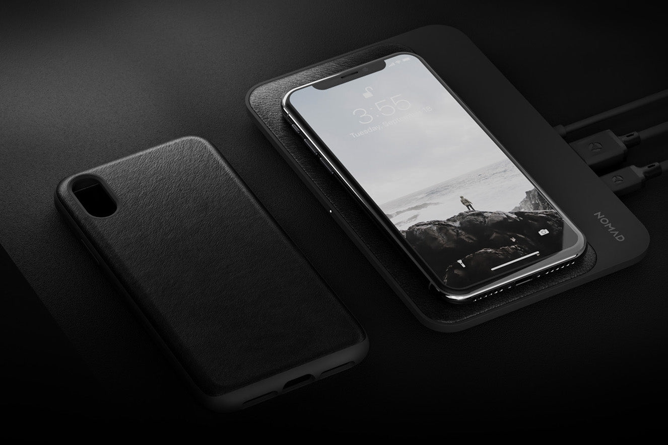 Black Iphone case and  Iphone on top of  Base Station
