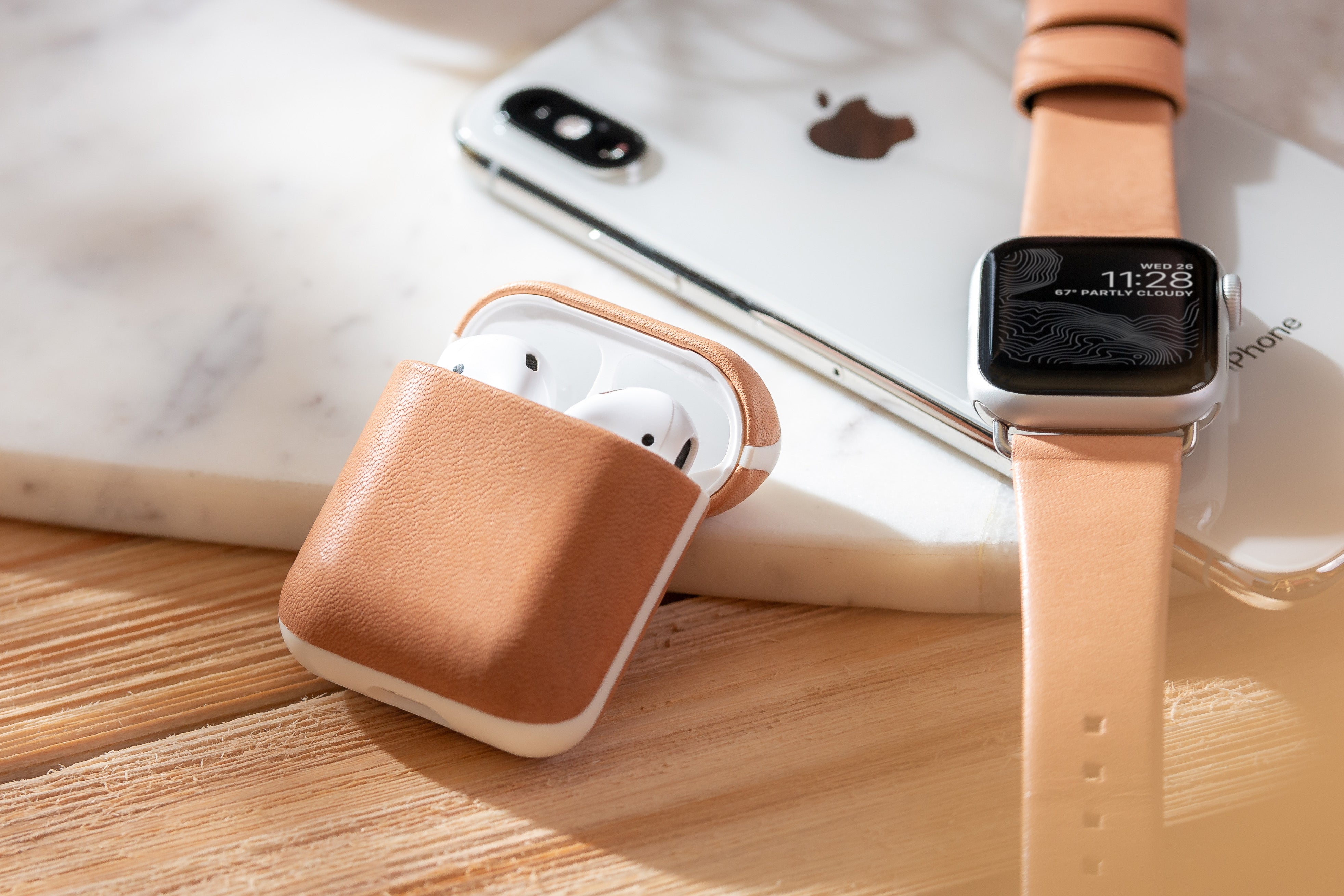 Open Rugged Case in Natural Nude for Apple Airpods next to an Apple Watch and iPhone