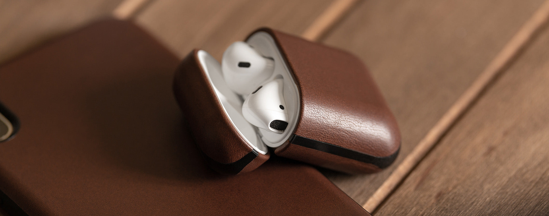 Close up of open Rugged Case in Rustic Brown for Apple Airpods leaning on an iPhone