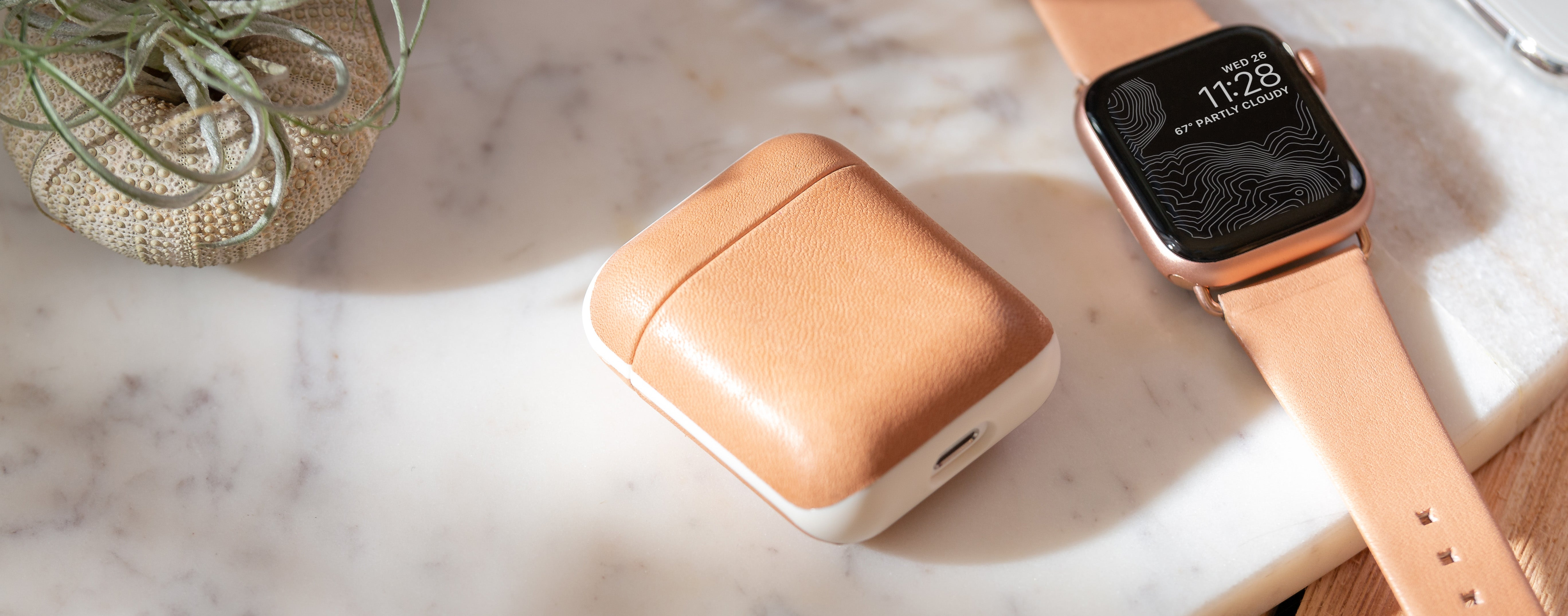 Closed Rugged Case in Natural Nude lying next to an Apple Watch