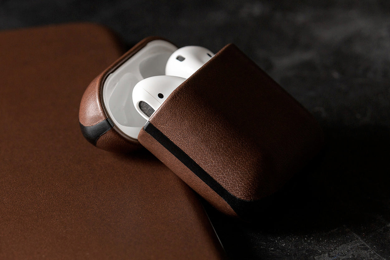 Open Rugged Case in Rustic Brown displaying Apple Airpods leaning on an iPhone