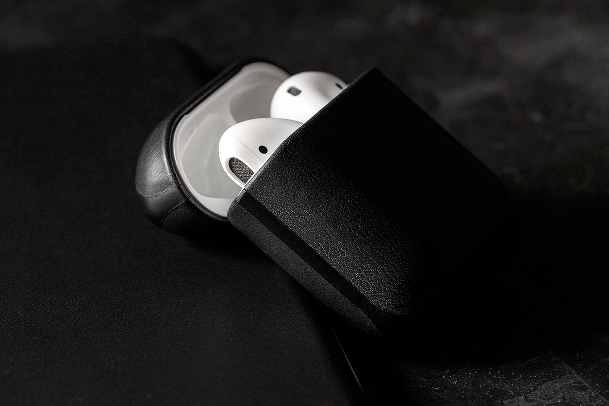 Open Rugged Case in Black displaying Apple Airpods leaning on an iPhone