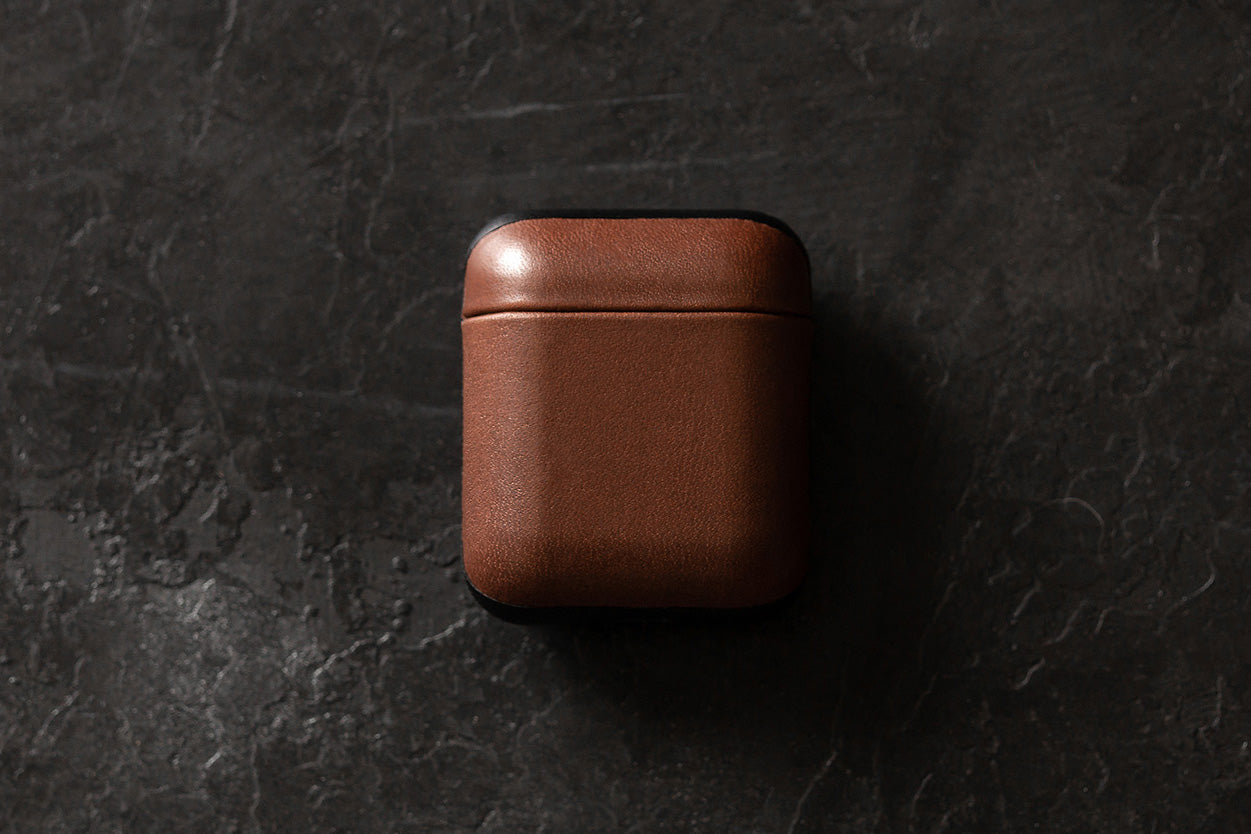 Closed Rugged Case in Rustic Brown for Apple Airpods on a table