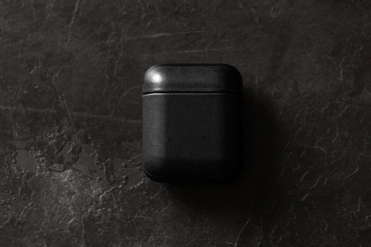 Closed Rugged Case in Black for Apple Airpods on a table