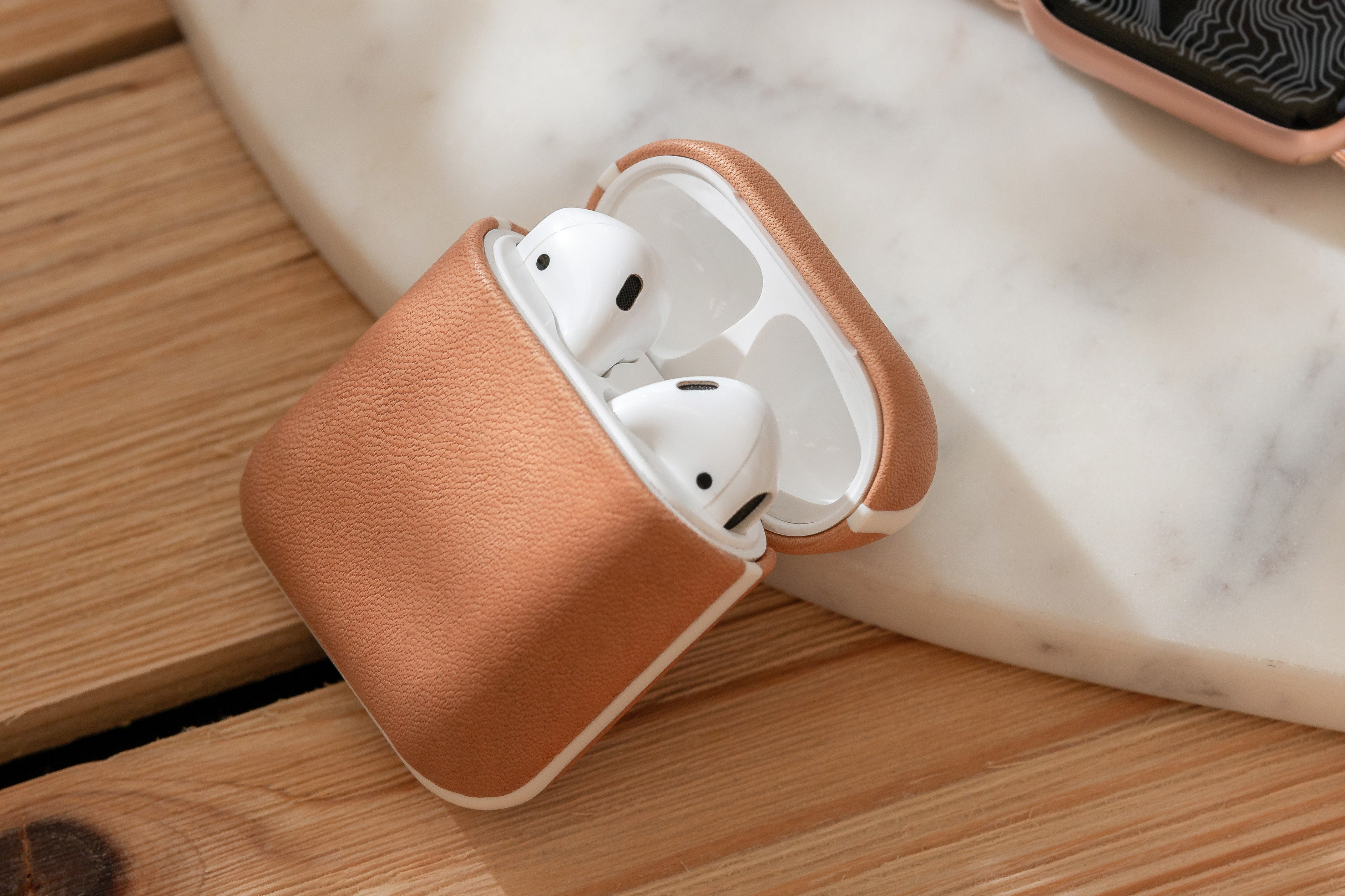 Open Rugged Case in Natural Nude displaying Apple Airpods leaning on a marble slab