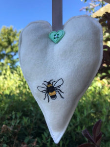 Fabric embroidered bee hanging heart.
