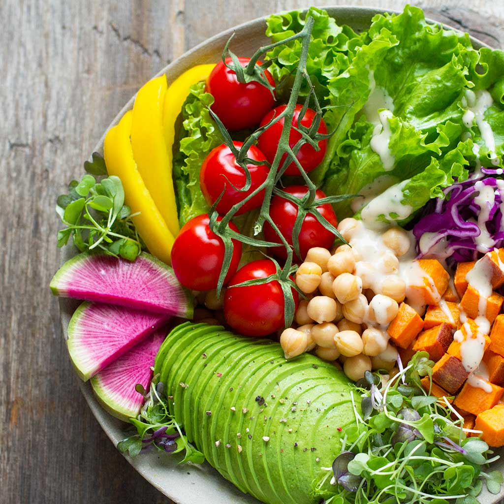 Fresh vegetable bowl with lettuce, cherry tomatoes, chickpeas, sweet potatoes, avocado, and more.