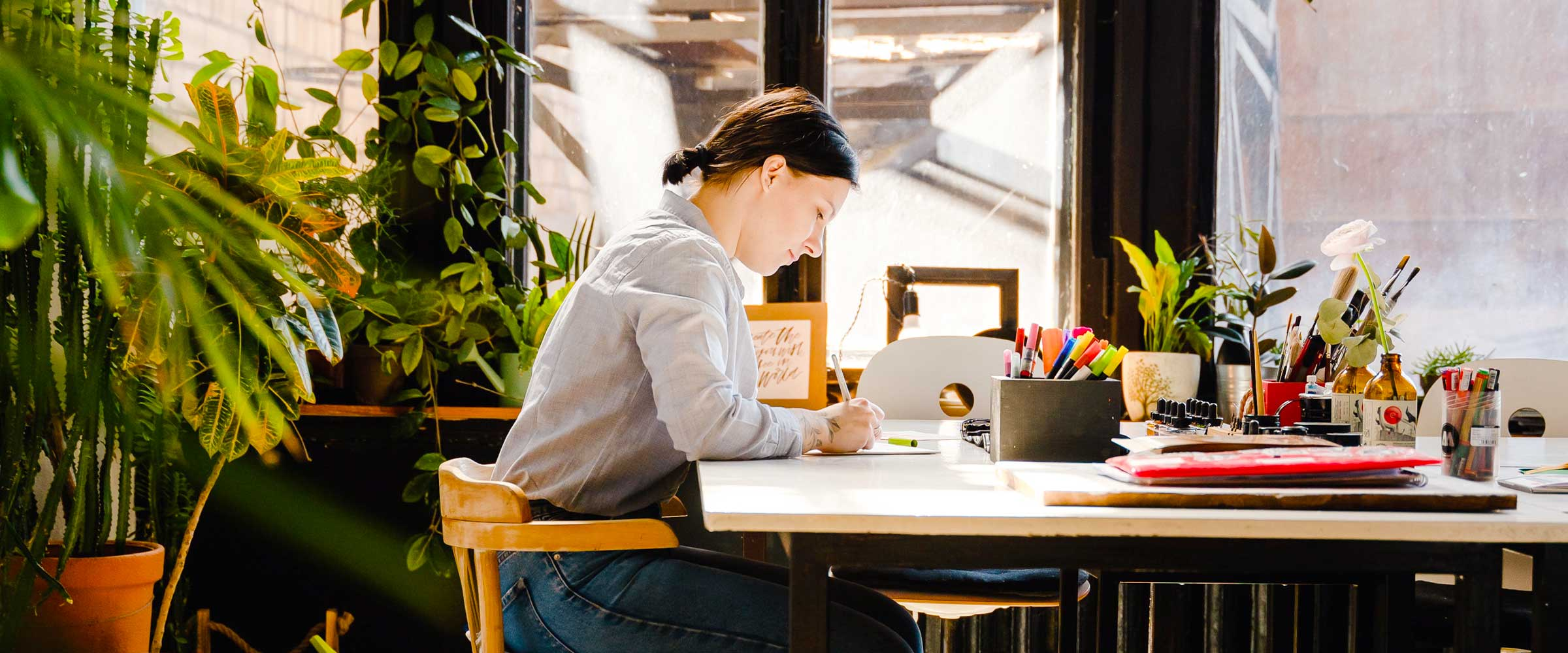 Woman sitting at desk, focusing on working, surrounded by plants.