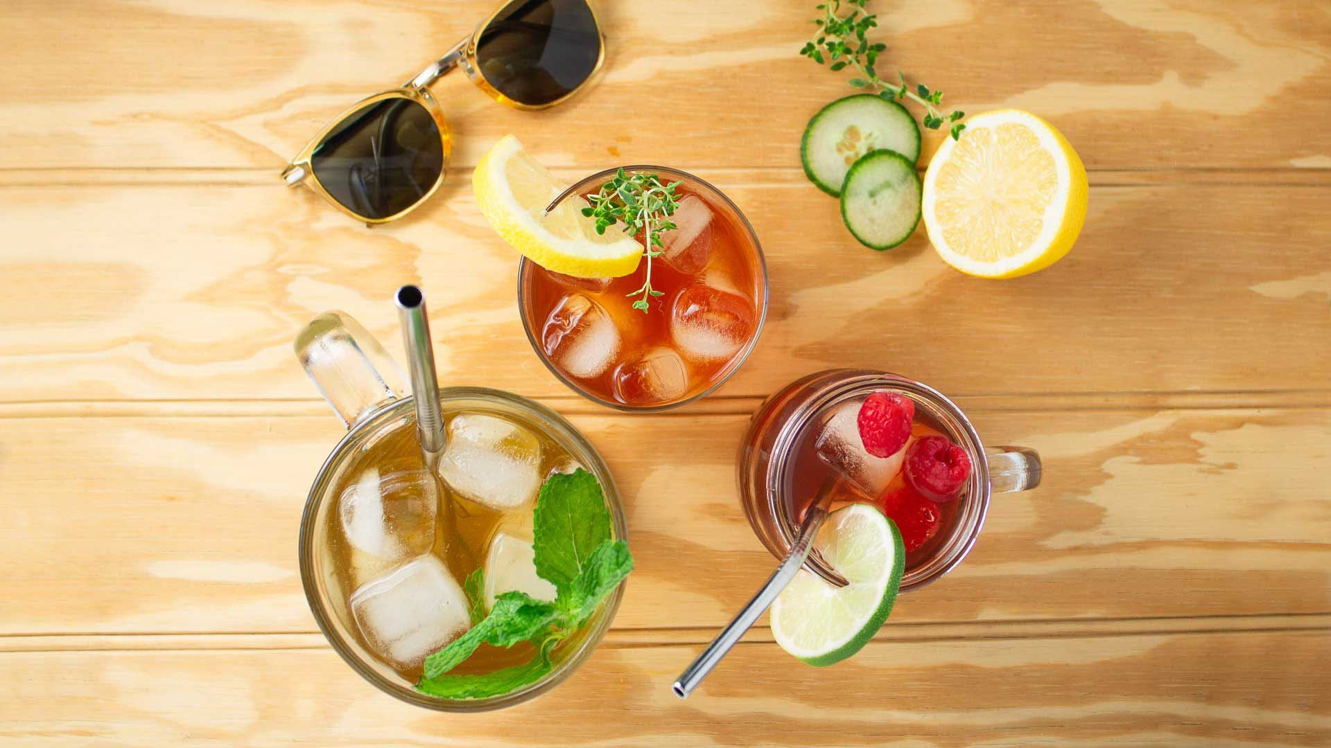 Clover adaptogenic iced tea, 3 different blends with fruit and herb garnishes in glasses on a wood background.