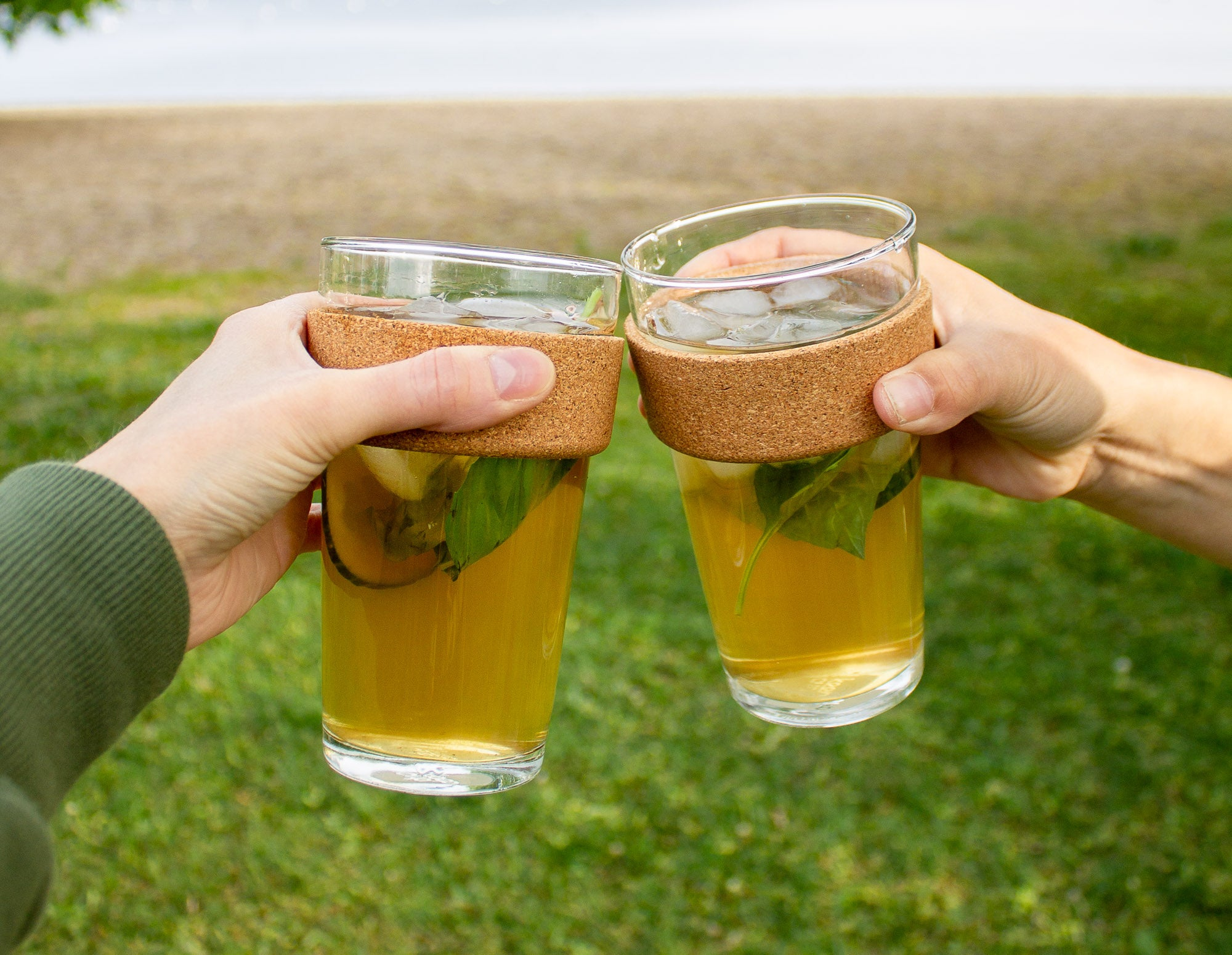 2 hands holding glasses of Clover adaptogenic iced tea, tapping to say cheers.