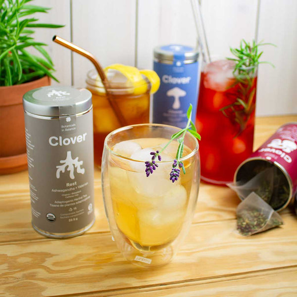 Clover iced tea blends Rest, Digest and Cleanse on a textured wooden surface.