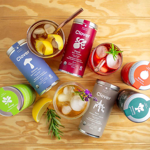Clover's 6 adaptogenic tea blend canisters with 3 glasses of iced tea on a textured wooden surface.