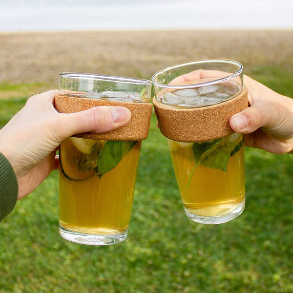 2 people's hands holding glass to go cups filled with clover iced tea, making a cheers gesture.