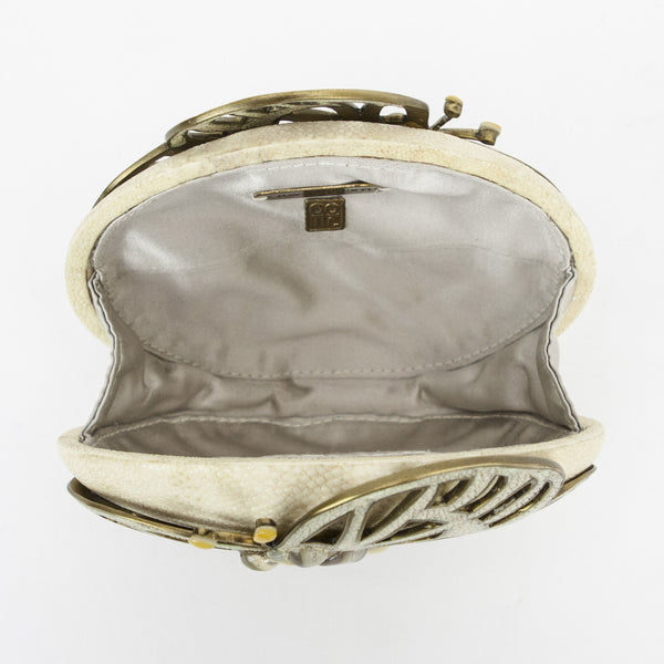 R & Y Augousti stingray hinged oval clutch with a cutout butterfly trimmed in brass tone and shell accents.