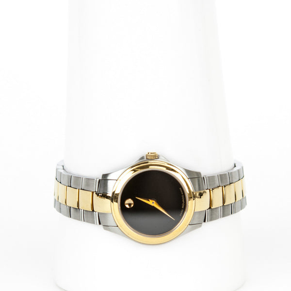 Movado two tone bracelet watch with gold plated bezel and hands, black museum dial with sapphire crystal, and butterfly clasp closure.