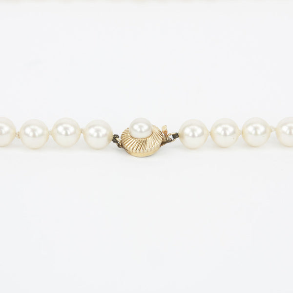 Knotted pearls with gold tone tab insert closure