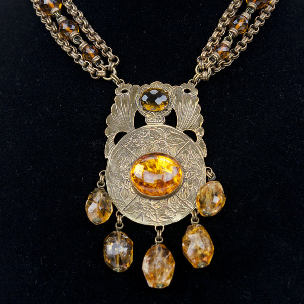 Brass tone necklace with filigree pendant with amber cabochon in the middle with dangling citrine