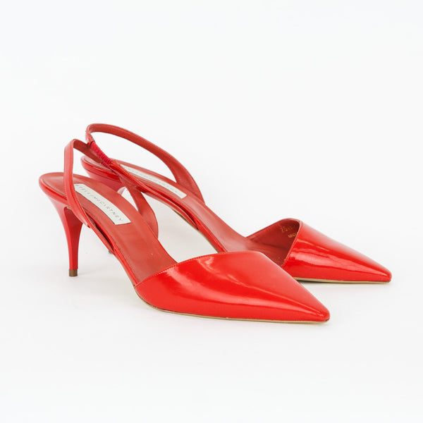 Asymmetrical Stella McCartney red patent faux leather d'Orsay slingback pumps with pointed toes, covered heels, and tonal stitching.