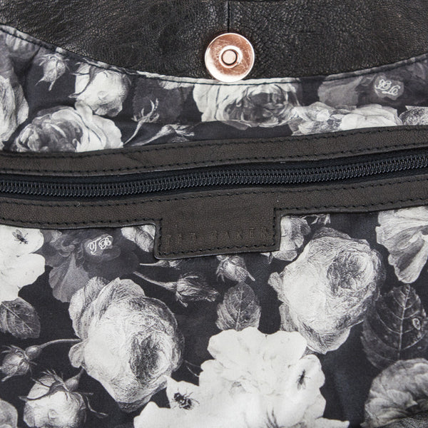 Fully lined in floral print with interior pocket with zip closure
