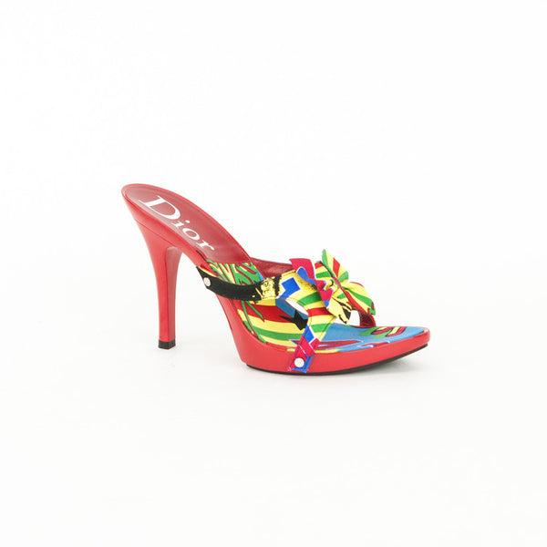 Christian Dior multi color print slide on sandals with open toes, accent bow across vamp, and red resin platform and heels.