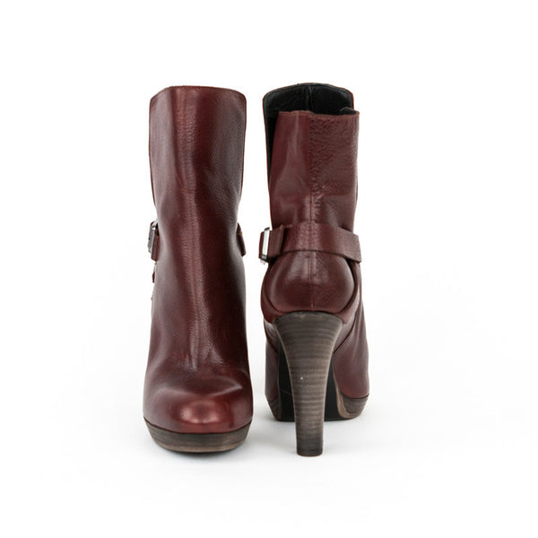 Amanda Gregory distressed leather burgundy booties with rounded toes, wooden stacked heels, and adjustable side buckle closures.