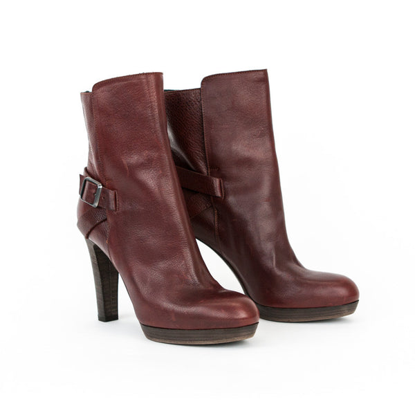 Amanda Gregory distressed leather burgundy booties with rounded toe, wooden stacked heel, and adjustable side buckle closure.